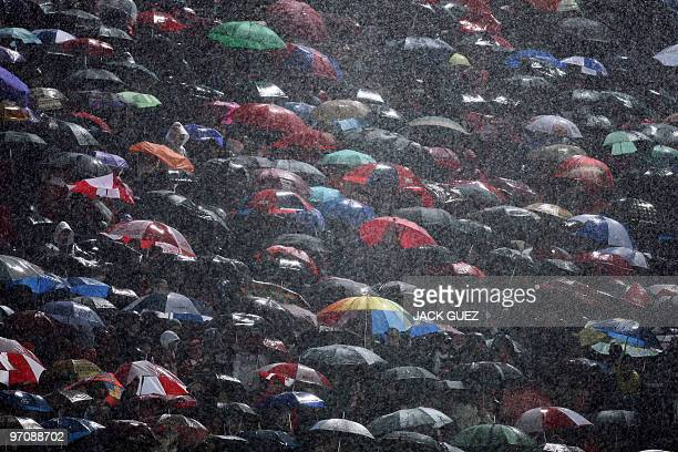 Heavy rain falls on football fan as they attend a UEFA Europa League football match between FC Rubin Kazan and Hapoel Tel Aviv on February 25 2010 at...