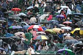 TOPSHOT A heavy rain shower falls on the spectators on centre court interrupting the men's singles third round match between Australia's John Millman...