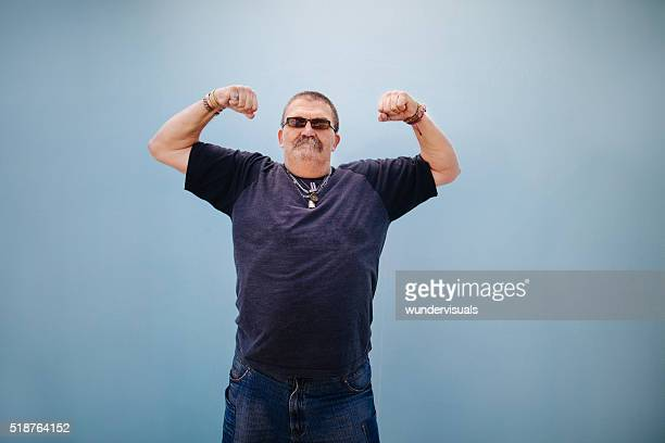 Heavy set older man showing his muscles