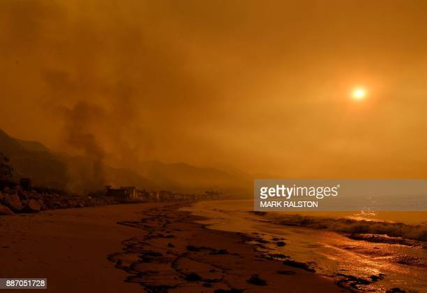 TOPSHOT Heavy smoke covers the seaside enclave of Mondos Beach beside the 101 highway as flames reach the coast during the Thomas wildfire near...
