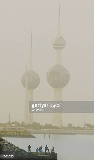 Heavy smoke from suspected oil well fires in southern Iraq blankets the Kuwait Towers as children play near the sea March 21 2003 in Kuwait City...