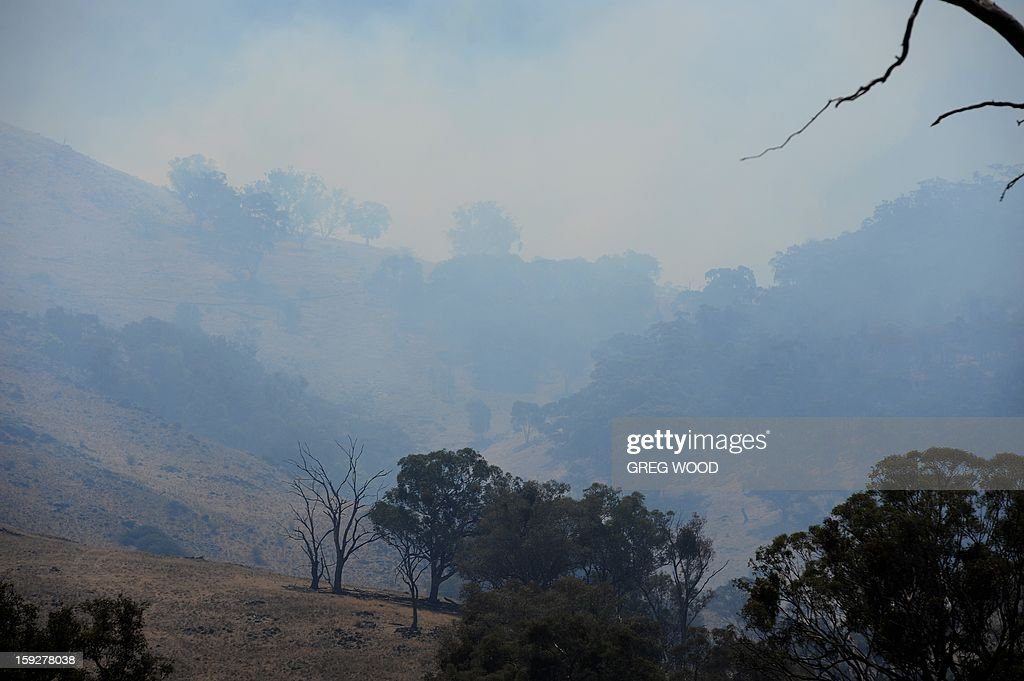 Heavy smoke hangs near where a scrubfire burns up a hillside south of Bookham, near Yass in the southern region of Australia's New South Wales state, on January 11, 2013. After two days of cooler weather, heat and high winds returned to much of the country as fire crews tackled the infernos that have been burning for a week, 18 of them out of control in the most populous state of New South Wales. AFP PHOTO / Greg WOOD
