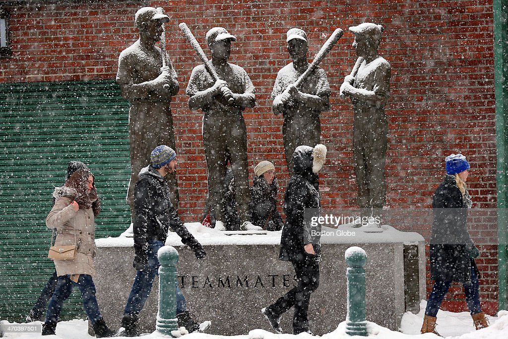 Heavy snow fell in the early afternoon as it dusted the shoulders of the Teammates statue outside Gate B at Fenway park at the intersection of Ipswich and Van Ness streets. Passersby pass by the statues which honor former Red Sox players Ted Williams, Johnny Pesky, Bobby Doerr and Dom DiMaggio.