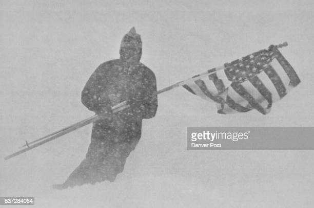 Heavy Snow Postpones Downhill RaceA skier carrying an American Flag is nearly lost in the heavy snowfall and fog as he makes his way down Aspen...