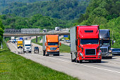 A steady flow of semis lead the way down a busy interstate highway in Tennessee.  Heat waves rising from the pavement give a nice shimmering effect to vehicles and forest behind the lead trucks.  Exce