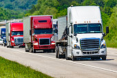 A solid line of eighteen-wheelers barrel down an interstate highway in Tennessee.  Heat waves rising from the pavement give a nice shimmering effect to vehicles and trees behind the lead truck.