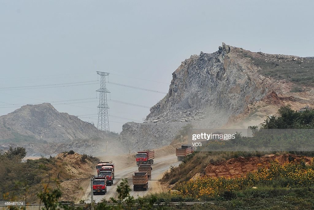 Heavy trucks carrying earthrock run at the construction site of Dalian's new airport on September 14 2014 in Dalian Liaoning province of China Dalian...