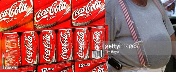 A heavyset man passes cartons of CocaCola displayed in a grocery June 13 2006 in Des Plaines Illinois Doctors at the annual American Medical...