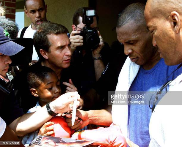 Heavyweight boxer Mike Tyson signs autographs for local boy Brandon Dillard aged 11 as he leaves his training camp gym in Cordova Memphis prior to...