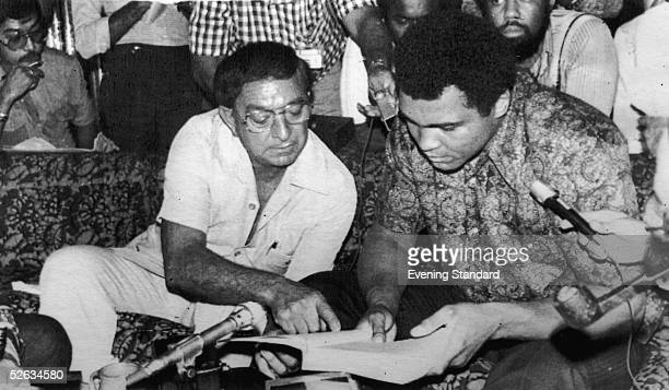 Heavyweight boxing champion Muhammad Ali looks at a book with his manager Angelo Dundee 25th June 1975
