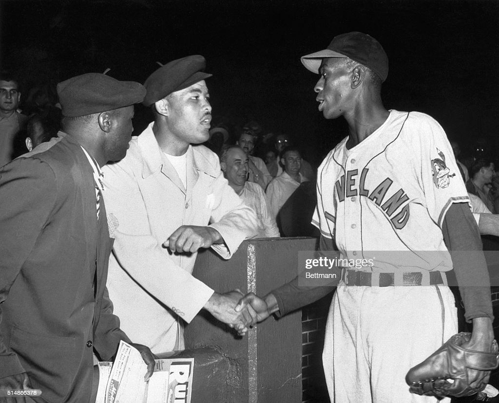 Heavyweight champ Joe Louis shakes the hand of Cleveland Indians pitcher Satchel Paige before a ballgame against the Chicago White Sox Paige will...