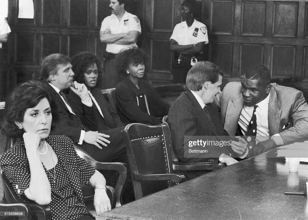 Heavyweight champ Mike Tyson (R) chats with his attorney, Steven Hayes, during a hearing in State Supreme Court here 7/21. Tyson is suing to dissolve his managerial contract with Bill Cayton. At left is Loraine Jacobs, widow of Jim Jacobs who was Tyson's co-manager, and seated behind Tyson are Donald Trump, Tyson's wife, Robin Givens, and Givens mother, Ruth Roper. During the 7/21 hearing, Tyson and Cayton received part of the purse from Tyson's bout with Michael Spinks.