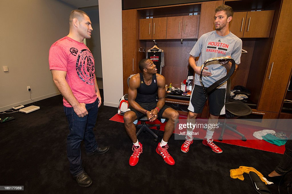 Heavyweight Champion <a gi-track='captionPersonalityLinkClicked' href=/galleries/search?phrase=Cain+Velasquez&family=editorial&specificpeople=5445619 ng-click='$event.stopPropagation()'>Cain Velasquez</a> (L), NBA Houston Rockets players <a gi-track='captionPersonalityLinkClicked' href=/galleries/search?phrase=Dwight+Howard&family=editorial&specificpeople=201570 ng-click='$event.stopPropagation()'>Dwight Howard</a> and <a gi-track='captionPersonalityLinkClicked' href=/galleries/search?phrase=Chandler+Parsons&family=editorial&specificpeople=4249869 ng-click='$event.stopPropagation()'>Chandler Parsons</a> interact with the UFC championship belt in the Houston Rockets locker room during the UFC 166 Ultimate Media Day at the Toyota Center on October 16, 2013 in Houston, Texas.