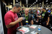 UFC heavyweight champion Cain Velasquez signs autographs for fans during the UFC Fan Expo 2014 during UFC International Fight Week at the Mandalay...