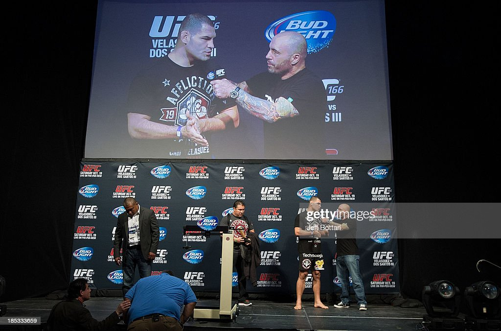 UFC heavyweight champion Cain Velasquez (2R) talks with Joe Rogan (R) on stage during the UFC 166 weigh-in at the Toyota Center on October 18, 2013 in Houston, Texas.