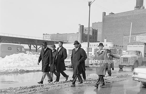 Heavyweight champion Cassius Clay surrounded by bodyguards arrive here to listen to Black Muslim leader Muhammad Elijah open a 3day Black Muslim...