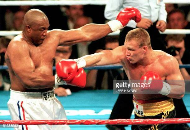 IBF heavyweight champion George Foreman of the US pulls back after taking a right from challenger Axel Schulz of Germany in the second round of their...