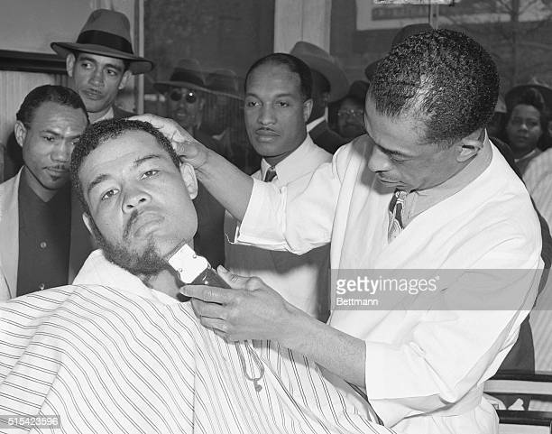 Heavyweight champion Joe Louis gets a nice growth of beard shorn off with an electric razor in the capable hands of his old friend William Herring...