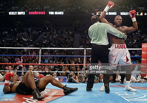 Heavyweight Champion Lennox Lewis of England is held by referee Eddie Cotton after knocking downs challenger Mike Tyson of the US during the 4th...