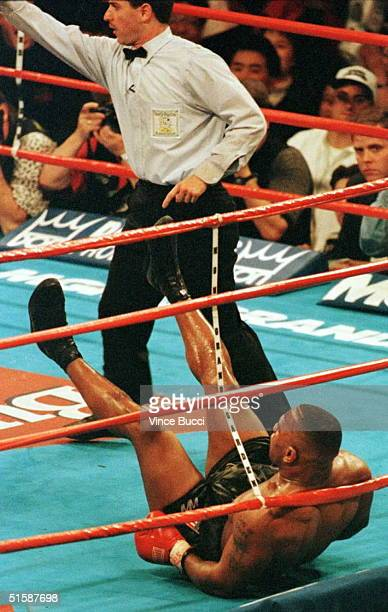 WBA heavyweight champion Mike Tyson is knocked down in the ring by challenger Evander Holyfield as referee Mitch Halpern orders Holyfield to a...
