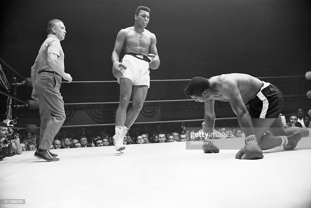 Heavyweight champion Muhammad Ali (c) dances away from the contender Floyd Patterson (r), after the former champion slipped and fell to his knees during the second round of their 1965 match in the Las Vegas Convention Hall.
