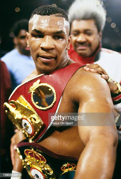 Heavyweight fighter Mike Tyson wears the championship belts after after a TKO of Frank Bruno in the third round of a scheduled twelve round WBC...
