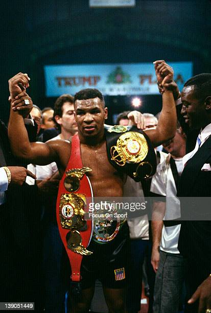 Heavyweight fighter Mike Tyson wears the championship belts after a fourth round TKO of Larry Holmes of a scheduled twelve round WBC WBA IBF...