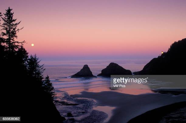 Heceta Head Lighthouse and full moon setting over ocean Devils Elbow State Park Oregon coast