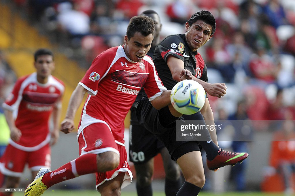 Hector Acosta (L) of Toluca struggles for the ball with Joe Corona (R) of Tijuana during a match Clausura 2013 Liga MX at Nemesio Diez Stadium on march 30, 2012 in Toluca, Mexico.