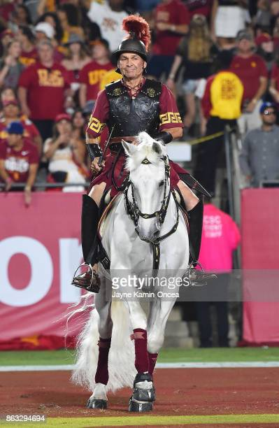 Hector Aguilar rides the USC Trojans mascot Traveler around the field after a touchdown in the game against the Utah Utes at the Los Angeles Memorial...