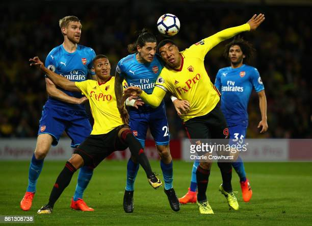 Hector Bellerin and Per Mertesacker of Arsenal battle with Troy Deeney and Richarlison de Andrade of Watford during the Premier League match between...