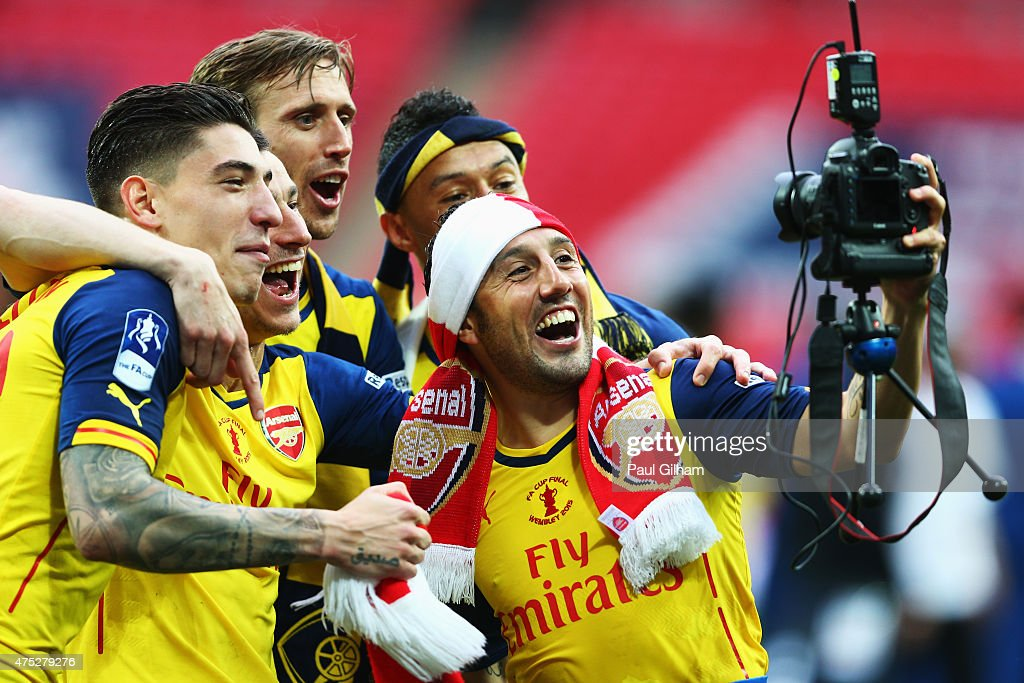 Hector Bellerin, Laurent Koscielny, Nacho Monreal, Alex Oxlade-Chamberlain and Santi Cazorla use a photographers camera as they celebrate victory after the FA Cup Final between Aston Villa and Arsenal at Wembley Stadium on May 30, 2015 in London, England. Arsenal beat Aston Villa 4-0.