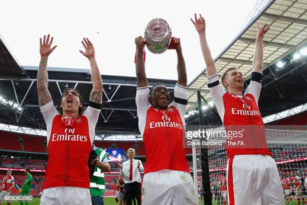 Hector Bellerin of Arsenal Danny Welbeck of Arsenal and Per Mertesacker of Arsenal celebrate with The FA Cup after the Emirates FA Cup Final between...