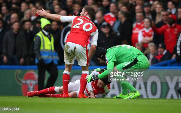 Hector Bellerin of Arsenal is helped by his team mates as he lies injured during the Premier League match between Chelsea and Arsenal at Stamford...