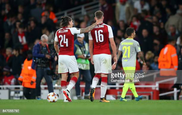 Hector Bellerin of Arsenal talks to Rob Holding of Arsenal as they walk off at half time during the UEFA Europa League group H match between Arsenal...