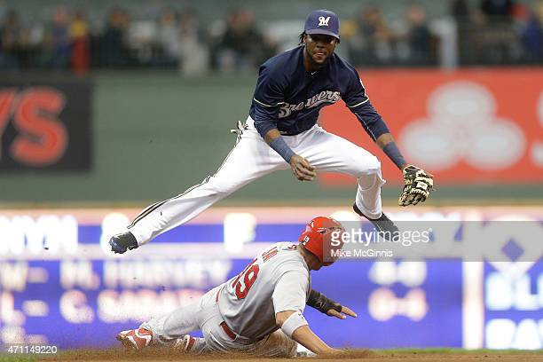 Hector Gomez of the Milwaukee Brewers jumps over Jon Jay of the St Louis Cardinals while turning the double play at second base during the fourth...