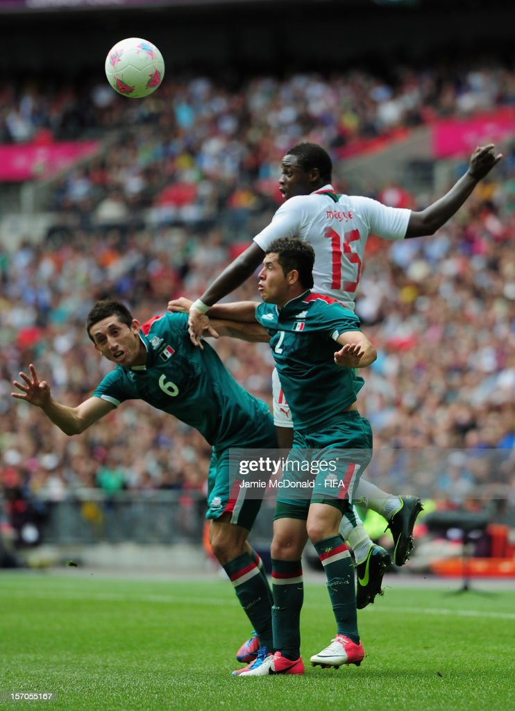Hector Herrera and <a gi-track='captionPersonalityLinkClicked' href=/galleries/search?phrase=Israel+Jimenez&family=editorial&specificpeople=5933961 ng-click='$event.stopPropagation()'>Israel Jimenez</a> of Mexico jumps with <a gi-track='captionPersonalityLinkClicked' href=/galleries/search?phrase=Magaye+Gueye&family=editorial&specificpeople=7018117 ng-click='$event.stopPropagation()'>Magaye Gueye</a> of Senagal during the Men's Football Quarter Final match between Mexico and Senegal, on Day 8 of the London 2012 Olympic Games at Wembley Stadium on August 4, 2012 in London, England.