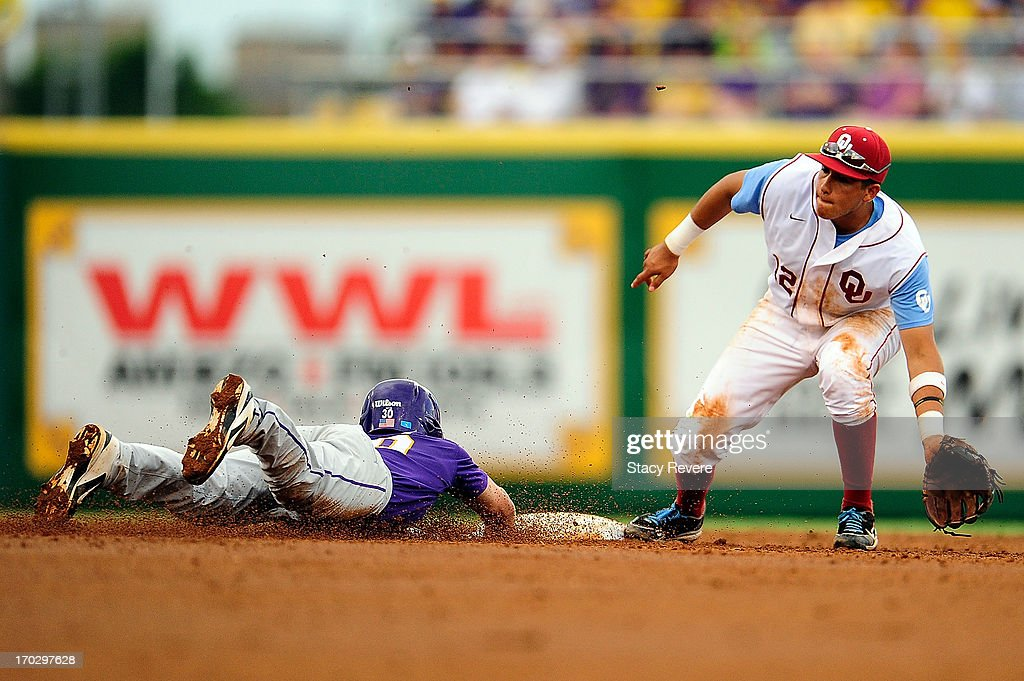 Hector Lorenzana #12 of the Oklahoma Sooners is unable to tag Alex Bregman #30 of the LSU Tigers during Game 2 of the NCAA baseball Super Regionals at Alex Box Stadium on June 8, 2013 in Baton Rouge, Louisiana.