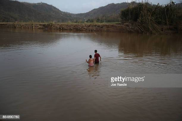 Hector Ojeda and Sonia Robles and Tony Ojeda cross a river on foot after the bridge was washed away when Hurricane Maria passed through on September...