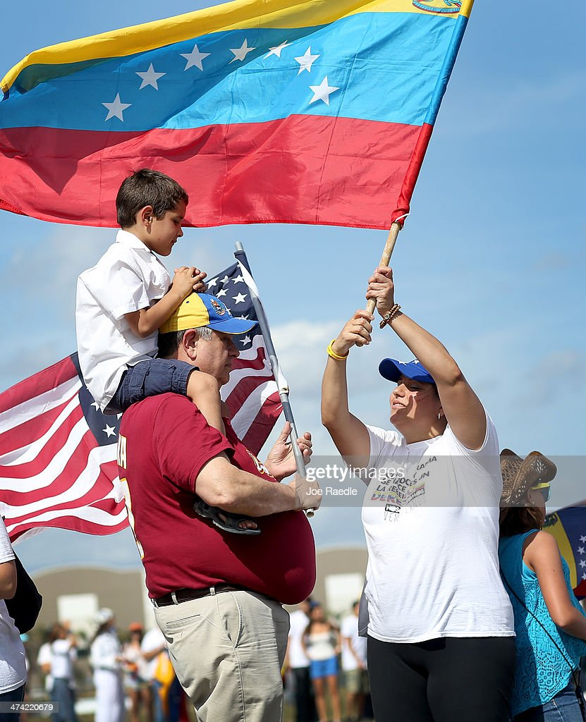 Hector Ramos stands with his grandson Emmanuel del Hierro and Maria del Hierro (R) as they and other Venezuelans along with their supporters show their support with the anti-government protests in Venezuela on February 22, 2014 in Doral, Florida. In Venezuela, protests over the past couple of weeks have resulted in violence as government opponents and supporters have faced off in the streets.