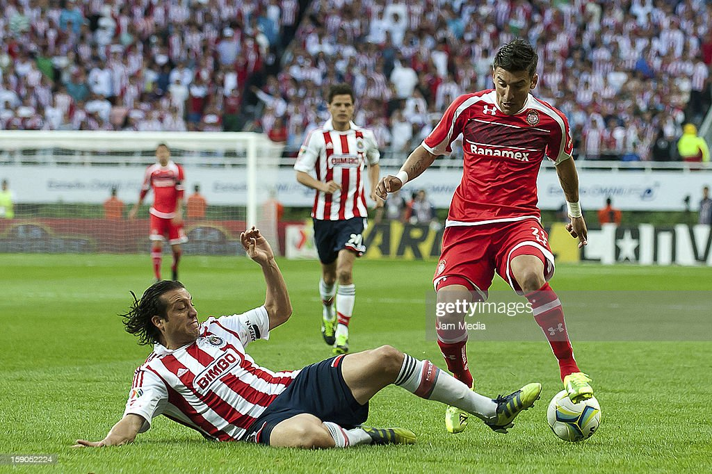 Hector Reynoso of Chivas struggles for the ball with <a gi-track='captionPersonalityLinkClicked' href=/galleries/search?phrase=Edgar+Benitez&family=editorial&specificpeople=3433635 ng-click='$event.stopPropagation()'>Edgar Benitez</a> of Toluca during the match between Chivas and Toluca as part of the Clausura 2013 Liga MX tournament at Omnilife Stadium on January 06, 2013 in Guadalajara, Mexico.