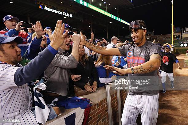 Hector Rondon of the Chicago Cubs celebrates with fans after defeating the St Louis Cardinals in game four of the National League Division Series to...