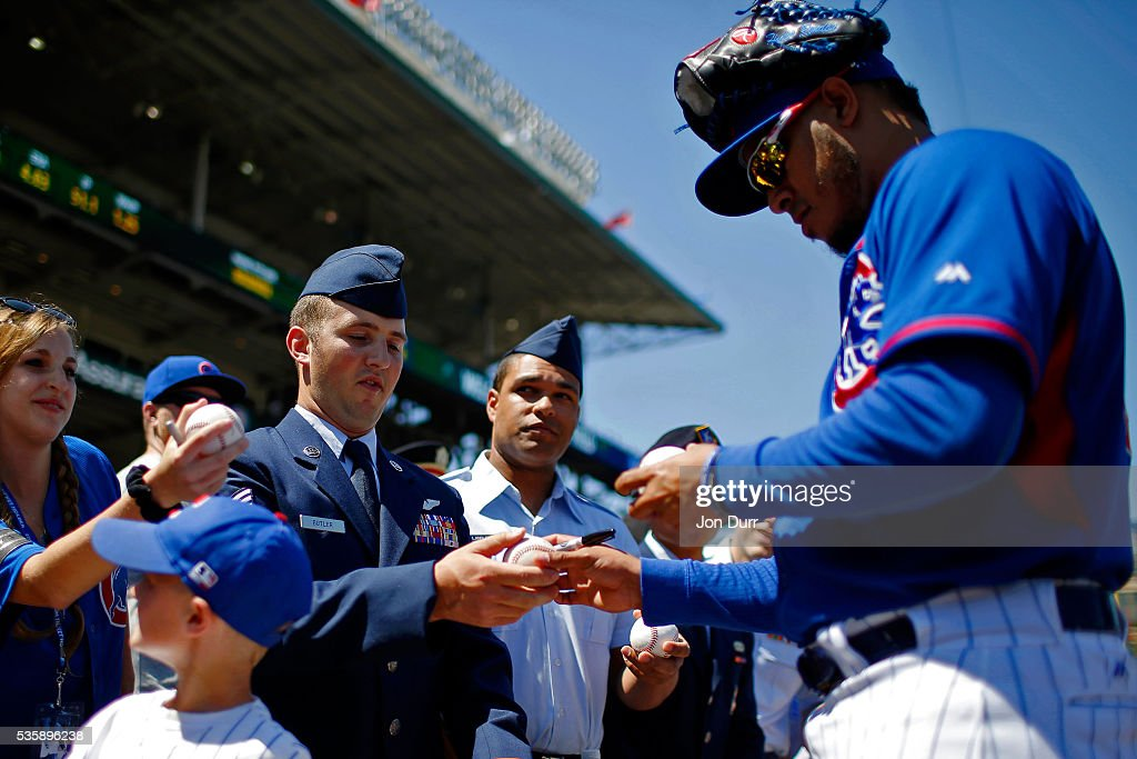 Hector Rondon #56 of the Chicago Cubs signs an autograph for a member of the military before the game between the Chicago Cubs and the Los Angeles Dodgers at Wrigley Field on May 30, 2016 in Chicago, Illinois.