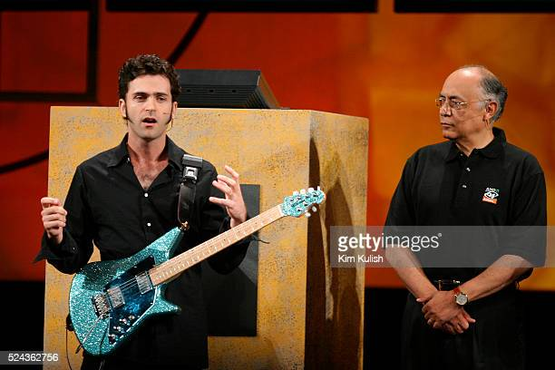 Hector Ruiz CEO of Advanced Micro Devices looks on as Dweezil Zappa son of legendary eclectic rocker Frank Zappa performs at the launch of the Athlon...