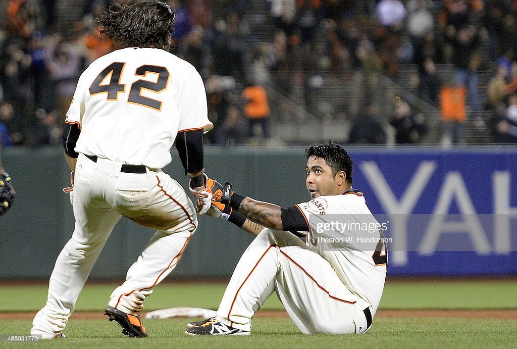 Hector Sanchez (R) and <a gi-track='captionPersonalityLinkClicked' href=/galleries/search?phrase=Brandon+Crawford&family=editorial&specificpeople=5580312 ng-click='$event.stopPropagation()'>Brandon Crawford</a> (L) of the San Francisco Giants celebrates after Sanchez hit an RBI walkk off single to score Crawford and defeat the Los Angles Dodgers 3-2 in twelve innings at AT&T Park on April 15, 2014 in San Francisco, California. Every team member is wearing jersey #42 in honor of Jackie Robinson Day.