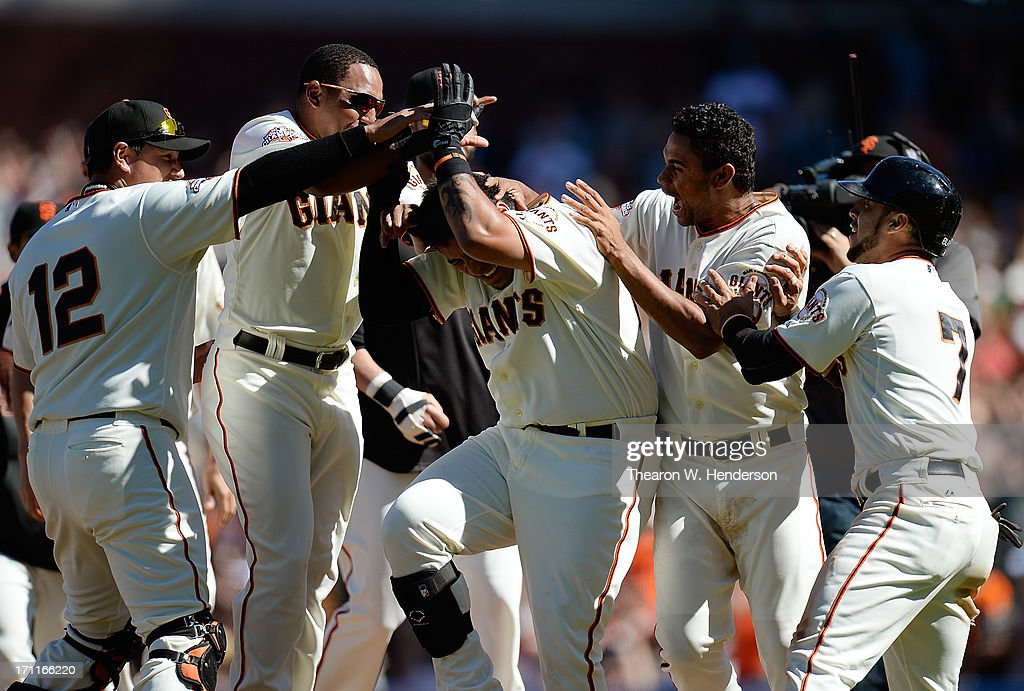 Hector Sanchez #29 (C), Gregor Blanco #7, Guillermo Quiroz #12 and teammates of the San Francisco Giants celebrate Sanchez hitting an RBI walk-off single scoring Gregor Blanco #7 in the bottom of the 11th inning to defeat the Miami Marlins 2-1 at AT&T Park on June 22, 2013 in San Francisco, California.