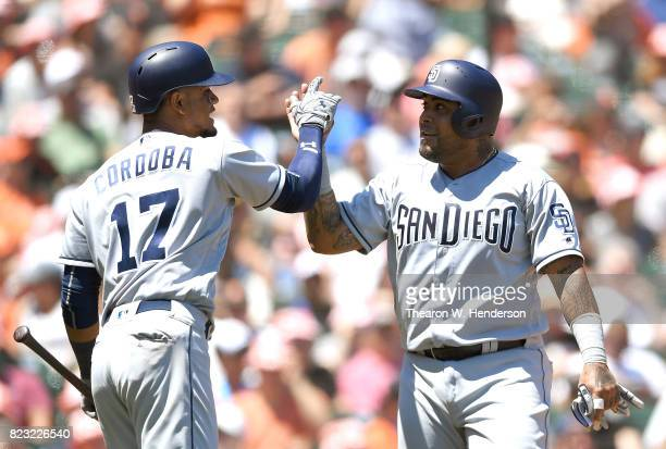 Hector Sanchez of the San Diego Padres is congratulated by Allen Cordoba after Sanchez scored against the San Francisco Giants in the top of the...