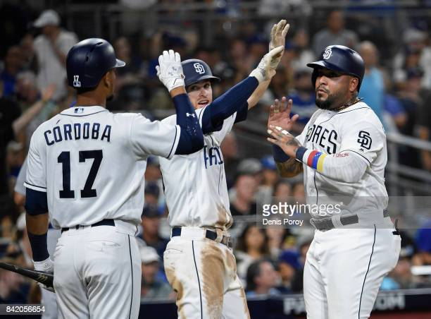 Hector Sanchez of the San Diego Padres right is congratulated by Cory Spangenberg center and Allen Cordoba after scoring during the third inning in...