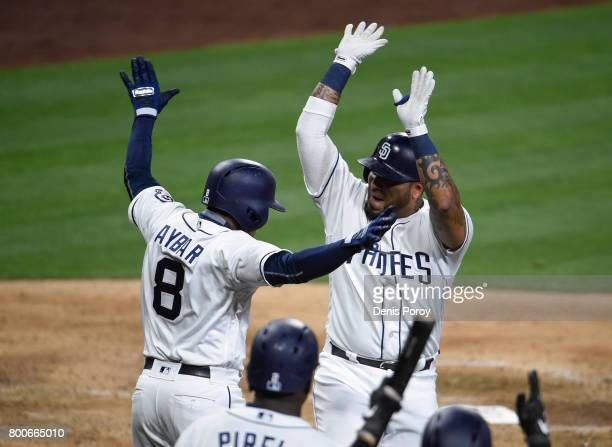 Hector Sanchez of the San Diego Padres right is congratulated by Erick Aybar after hitting a tworun home run during the eighth inning of a baseball...