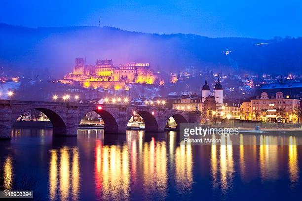 Heidelberg Castle and Alt Brucke (Old Bridge) over Neckar River at dusk.